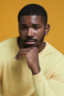 Vertical portrait of handsome africanamerican man looking at camera while posing resting chin on han...