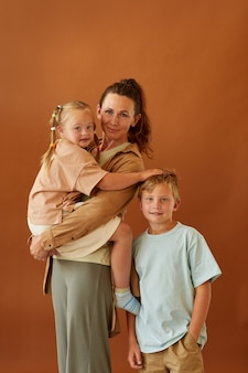 Vertical portrait of happy mature mother holding daughter with downs syndrome and smiling son while standing against plain brown surface in studio