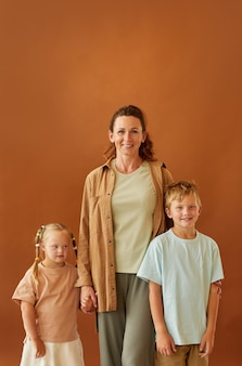 Vertical portrait of happy mature mother hugging daughter with downs syndrome and smiling son while standing against plain brown surface in studio