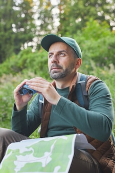 Vertical portrait of mature man holding binoculars and map while hiking alone in forest