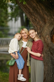 Vertical portrait of modern adult mother with two daughters posing together smiling happily while standing by tree outdoors enjoying family time in park