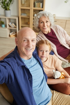 Vertical portrait of modern senior couple taking selfie with cute red haired girl in home interior