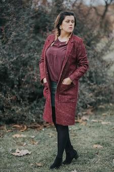 가을에 숲에서 치마, 부츠, 코트를 입은 갈색 머리 젊은 여성의 세로 초상화