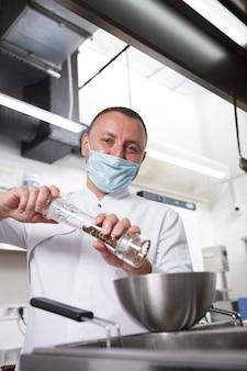 Вертикальный портрет шеф-повара в медицинской маске для лица, соления приготовленной еды на кухне ресторана