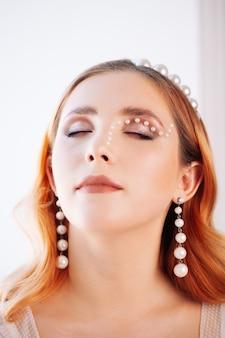 Вертикальный портрет крупным планом рыжеволосой женщины с закрытыми глазами с макияжем из жемчуга и пе ...