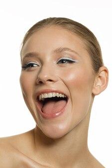 完璧な肌を持つ幸せな笑顔の女の子の縦の肖像画。白い背景の上の肖像画。高品質の写真