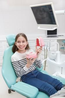 Вертикальный портрет счастливой молодой девушки, сидящей в стоматологическом кресле, держа модель зубных протезов