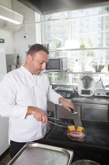 Вертикальный портрет профессионального шеф-повара, готовящего говядину и кукурузу на гриле в ресторане