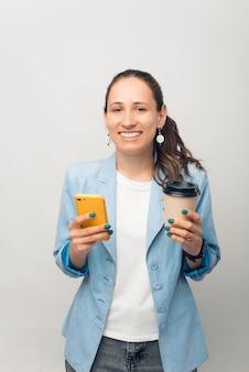 커피 브레이크 동안 그녀의 전화를 사용 하 여 웃는 여자의 세로 초상화.