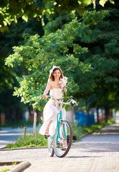 Вертикальный портрет женщины, весело улыбаясь, наслаждаясь на велосипеде в парке летом