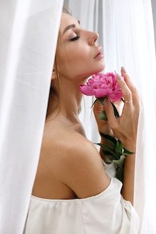 ピンクの牡丹のクローズアップを持つ女性の縦の肖像画
