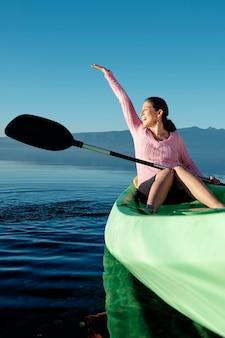 Вертикальный портрет молодой женщины в каяке с распростертыми объятиями, счастливо наслаждающейся жизнью.