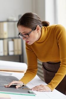 사무실에서 책상에서 작업하는 동안 청사진 및 계획을 그리기 성인 여성 건축가의 세로 초상화
