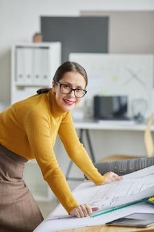 사무실에서 드로잉 책상에 기대어 청사진에서 작업하는 동안 카메라에 웃 고 성인 여성 건축가의 세로 초상화