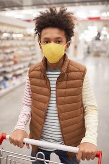 Вертикальный портрет афро-американского мальчика в маске в супермаркете, смотрящего в камеру, толкая тележку для покупок