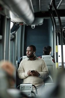 도시에서 대중 교통으로 여행하는 동안 버스에서 창을보고 아프리카 계 미국인 남자의 세로 초상화
