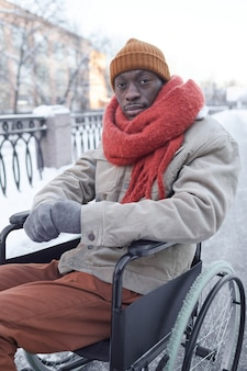 Вертикальный портрет афро-американского мужчины, использующего инвалидную коляску на открытом воздухе зимой и смотрящего в камеру, копией пространства