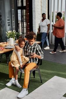 家族の集まりの間に妹と遊んでいるアフリカ系アメリカ人の10代の少年の縦の肖像画...
