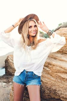 石の背景にポーズをとって長い髪を持つ魅力的なブロンドの女の子の垂直の肖像。彼女はカメラに微笑んでいます。