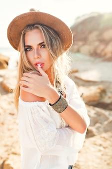 人けのないビーチで日光の背景にカメラにポーズをとって長い髪を持つ魅力的なブロンドの女の子の垂直の肖像。