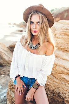 人けのないビーチの石の上に座って長い髪を持つ魅力的なブロンドの女の子の垂直方向の肖像画。彼女はカメラを見ています。