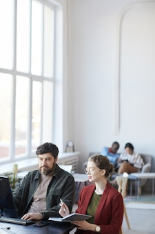 Вертикальный портрет бородатого бизнес-менеджера, разговаривающего с коллегой во время встречи за столом в белом интерьере офиса, копией пространства