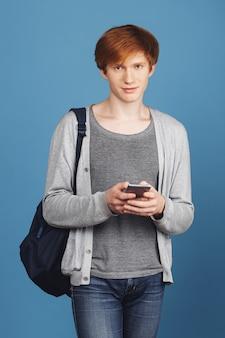 Вертикальный портрет красивого серьезного молодого студента парень с рыжими волосами в повседневной одежде с черным рюкзаком в чате с подругой по телефону, со спокойным выражением лица
