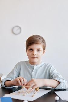 학교에서 미술과 공예 수업을 즐기고 카메라를 보고 있는 소년의 세로 초상화, 공간 복사