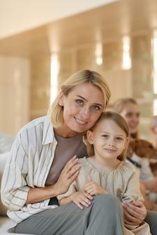 Вертикальный портрет беззаботной молодой женщины, обнимающей милую дочь в домашнем интерьере с семьей