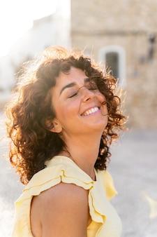 白い歯の笑顔で陽気な女性の縦の肖像画。旅行と休日の幸福の概念