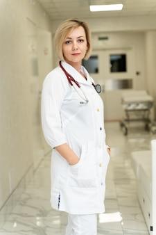 現代の病院に立って、機嫌の良いカメラに微笑んでいる陽気な若い白人女性専門看護師または医療助手の縦の肖像画。医師のコンセプト
