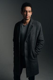 검은색 외진 배경에 주머니에 손을 넣고 세련된 긴 코트를 입은 자신감 있는 청년의 세로 초상화. 멀리 찾고 포즈 심각한 백인 남성의 전체 길이 스튜디오 샷.