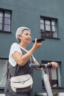 Вертикальный портрет современной зрелой женщины, говорящей по смартфону во время езды на электросамокате в городе