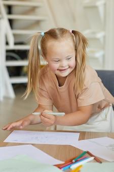 Вертикальный портрет милой блондинки с синдромом дауна, рисующей и счастливо улыбающейся, наслаждаясь уроком развития
