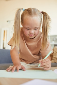 Вертикальный портрет симпатичной блондинки с рисунком или письмом с синдромом дауна во время упражнений на развитие дома
