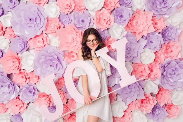 かわいいブルネットの少女の垂直方向の肖像画。彼女は立って、広く笑っている木の言葉「喜び」を持っています。ピンクの花の背景