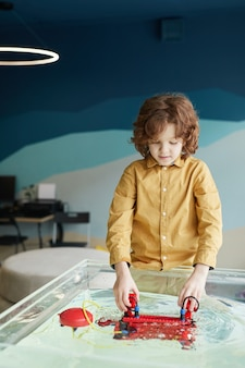 Вертикальный портрет симпатичного кудрявого мальчика, опускающего роботизированную лодку в воду во время экспериментов с технологиями в лаборатории робототехники в школе