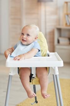 Вертикальный портрет милого маленького ребенка, сидящего на высоком стуле в ожидании еды, глядя на что-то