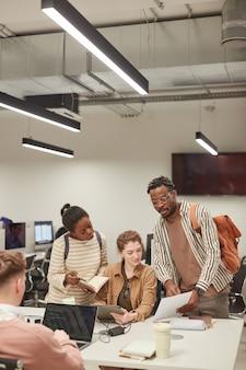 Вертикальный портрет разнообразной группы студентов, работающих вместе в современной школьной библиотеке и использующих компьютеры, копировальное пространство
