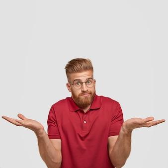 困惑した無知な表情の疑わしいセクシーな男性の縦の肖像画、何かに不安を感じ、丸い眼鏡と赤いtシャツを着て、空白の白い壁に立っています