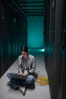 Вертикальный портрет женщины-инженера по данным, использующей ноутбук, сидя на полу в серверной и настраивая суперкомпьютерную сеть, скопируйте пространство