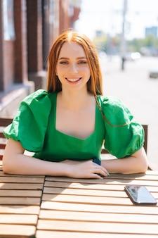 Вертикальный портрет счастливой улыбающейся молодой женщины, сидящей за столом на террасе открытого кафе в солнечный летний день и смотрящей на камеру, размытый фон, выборочный фокус.