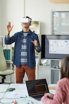 Вертикальный портрет команды ит-разработчиков, разрабатывающей программное обеспечение для погружения в реальность, с акцентом на мужчину с гарнитурой vr в офисе