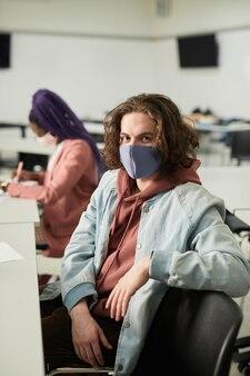 학교에서 마스크를 쓰고 교실 책상에 앉아 카메라를 바라보는 장발 청년의 세로 초상화