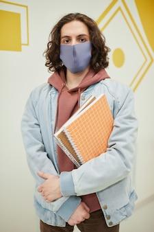 학교에서 마스크를 쓰고 벽에 기대어 공책을 들고 있는 장발 청년의 세로 초상화