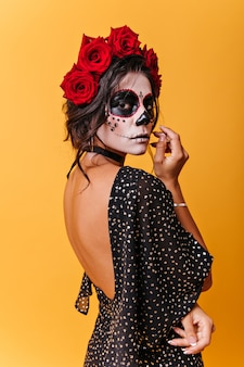 彼女の頭にバラを持つメキシコの女性の縦の肖像画。カーニバルマスクの女の子が思慮深くポーズをとる