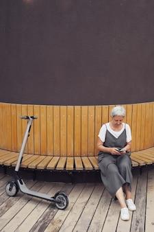 Вертикальный портрет современной зрелой женщины, использующей смартфон, отдыхая на скамейке на открытом воздухе с электросамокатом на переднем плане