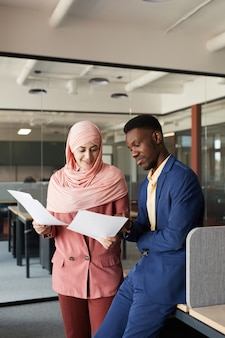 アフリカ系アメリカ人の同僚と話し、オフィスのインテリアに立ってドキュメントについて話し合う現代のイスラム教徒の実業家の縦の肖像画