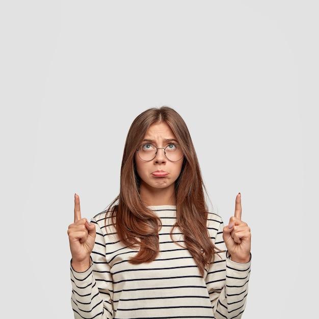 Вертикальный портрет обиженной, оскорбленной недовольства европейской женщины недовольно смотрит вверх, одетая в полосатый черно-белый свитер