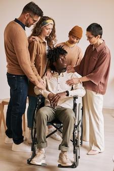 지원 그룹에서 치료 세션 동안 휠체어에 젊은 남자를 위로하는 사람들의 세로 초상화